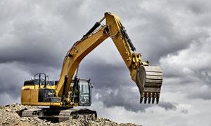 多云天空下在作业的挖掘机高清图片