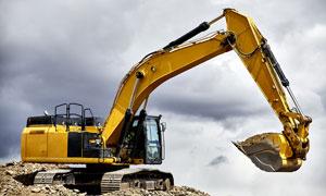 阴沉沉天空下作业的挖掘机高清图片