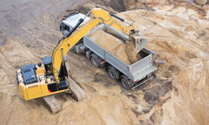 在往车上倾倒沙子的挖掘机高清图片