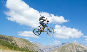 蓝天白云与空中的自行车手高清图片