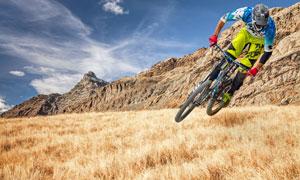 蓝天白云山峦与自行车车手高清图片