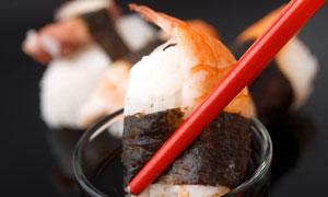 筷子夹起来蘸料的寿司摄影高清图片