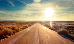 荒凉草原上的公路风光逆光高清图片