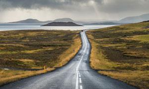 公路与阴云密布的湖泊摄影高清图片