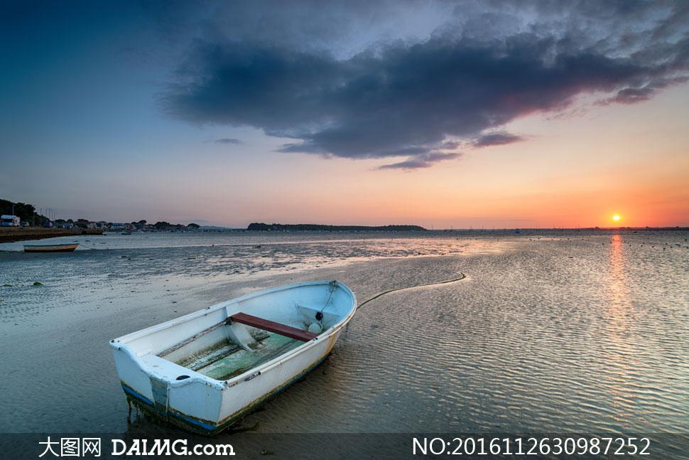 落日余晖下的海边小船摄影高清图片