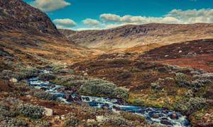 蓝天白云与山间的涓涓溪流摄影图片