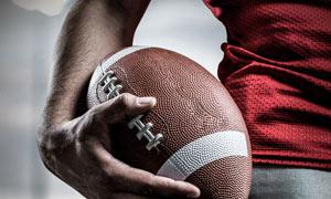 拿着橄榄球的球员局部特写高清图片