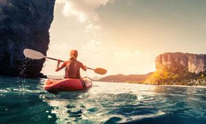 水面上划着小艇的人物摄影高清图片