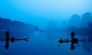 清晨在湖泊中打渔的渔民摄影图片