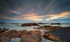 海边晚霞和礁石摄影图片