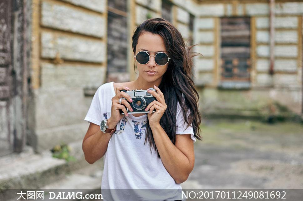 拿着照相机的秀发美女摄影高清图片
