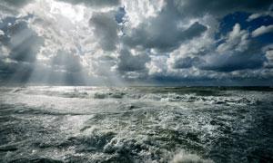 从云层洒落到海面上的阳光高清图片