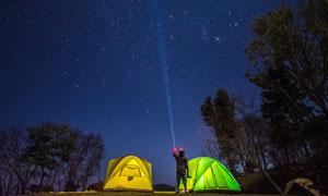 用探照灯照向夜空的露营者高清图片