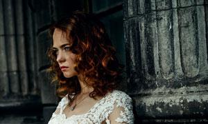 靠着罗马柱的美女新娘摄影高清图片