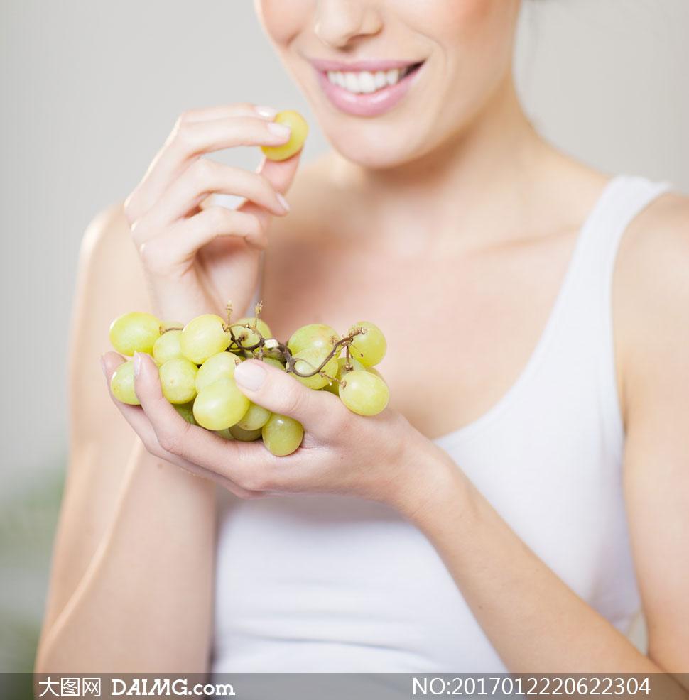 手捧着葡萄串吃起来的美女高清图片