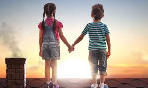 屋顶上手拉手的男孩与女孩高清图片