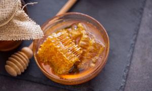 搅拌棒与在玻璃碗里的蜂蜜高清图片