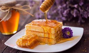 盘子里淋有蜂蜜的甜品摄影高清图片