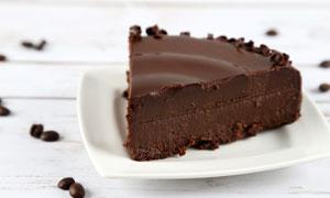 咖啡豆与切开的巧克力蛋糕高清图片