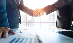 在谈判桌上握手的商务人物高清图片