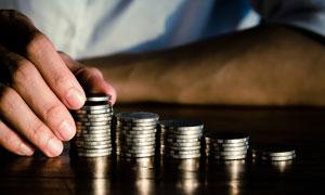 把硬币叠成柱状的人物摄影高清图片