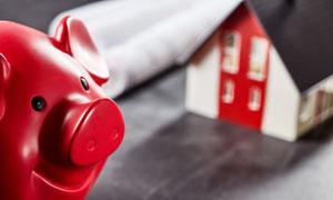 房子模型与红色小猪存钱罐高清图片