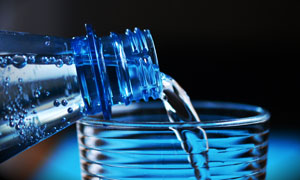 正往杯子里注水的水瓶特写高清图片