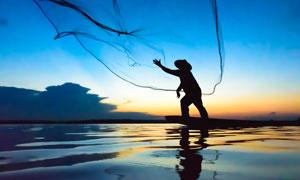 湖面上撒网捕鱼的渔夫剪影高清图片