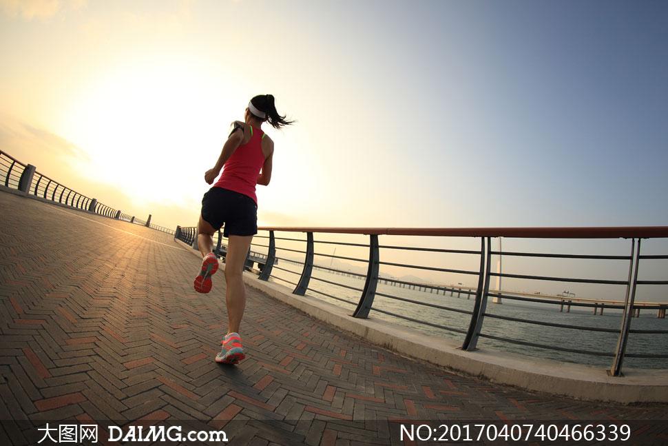 在海边跑步的人物背影摄影高清图片