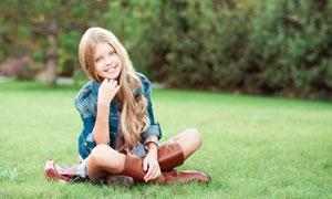 盘腿坐在草坪上的长发女孩高清图片