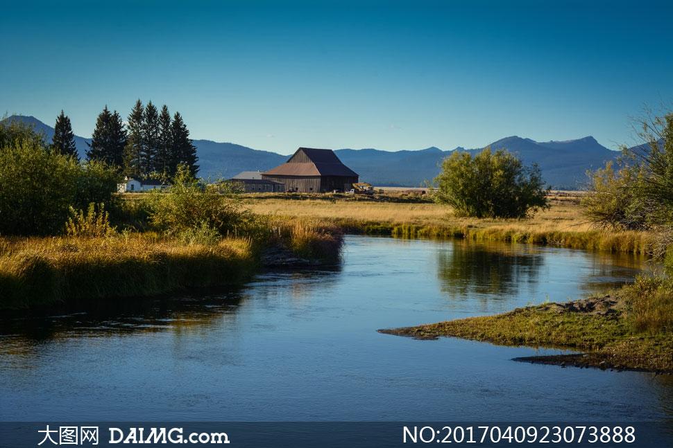 小河树木房子与远处的大山高清图片