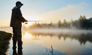 黄昏在河边钓鱼的男人摄影高清图片