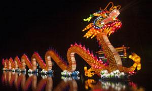 在夜晚灯光点亮的龙舟摄影高清图片