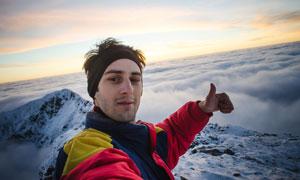 以山顶风光做背景的登山者高清图片
