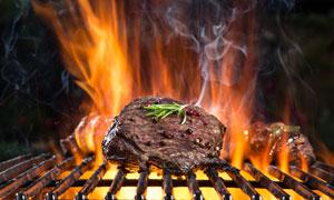 烧烤架上大火烤的牛排摄影高清图片