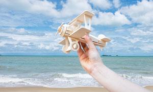 蓝天与手里的木质飞机模型高清图片