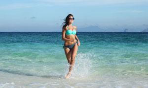 走在沙滩海水中的墨镜泳装高清图片