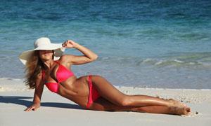海边沙滩上的红色泳装美女高清图片