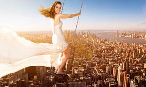 在城市上空玩荡秋千的美女创意图片