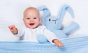 与针织玩具兔躺一起的宝宝高清图片
