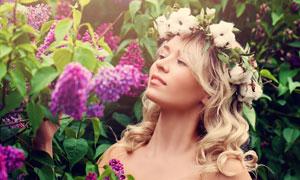在闻着花香的金发美女摄影高清图片