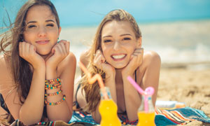 沙滩上双双托着下巴的美女摄影图片