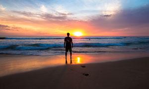 海边观看日落美景的人摄影图片