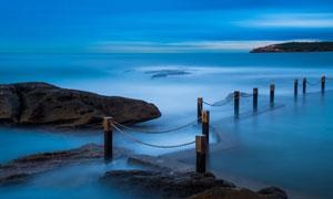 蓝色唯美海边和木桩摄影图片