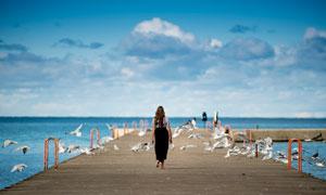 在海边木桥上散步的美女摄影图片