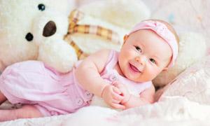 靠著玩具熊的可愛寶寶攝影高清圖片