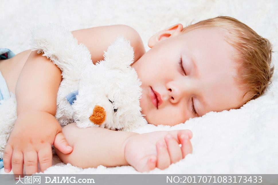 抱着玩具熊睡着的宝宝摄影高清图片
