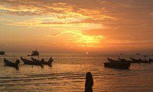 夕阳下的海边渔船摄影图片