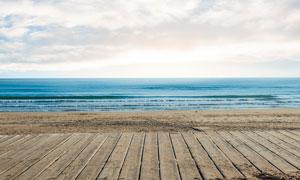 蓝天下的海洋和木地板摄影图片