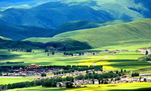 山脚下草原景色和村庄摄影图片
